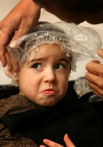 Rick Conroy puts a shower cap on Alyssa, 3, after putting a head lice treatment on her hair.  She had to keep the cap on for 10 minutes.  Conroy then rinsed her hair and combed it out, checking for lice.  Nitpickin, believed to be the only head lice removal center in Ohio, opened last week in downtown Willoughby, Ohio.   Monday, February 18, 2008  (Chris Stephens/The Plain Dealer)